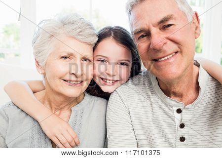 Portrait of smiling grandparents and granddaughter on the sofa