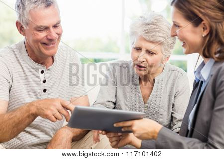 Businesswoman showing tablet to senior couple at home