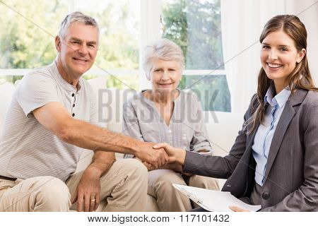 Businesswoman and senior man handshaking at home