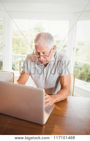 Focused senior man using laptop at home