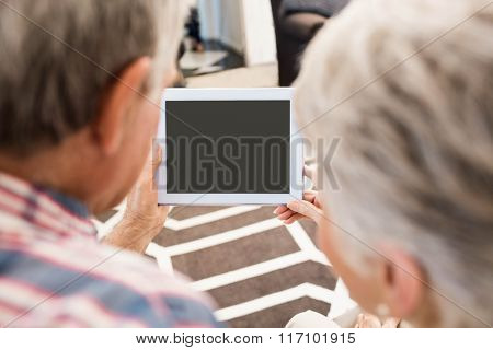 Rear view of senior couple using tablet at home