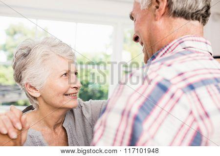Smiling senior couple dancing at home