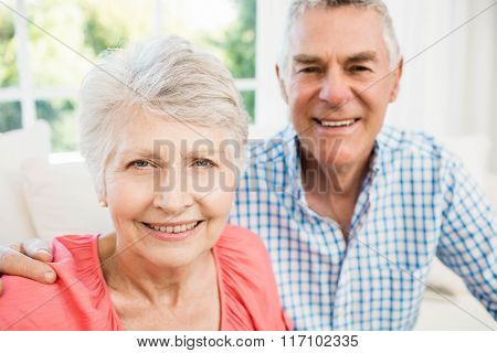 Happy senior couple taking a selfie on the sofa