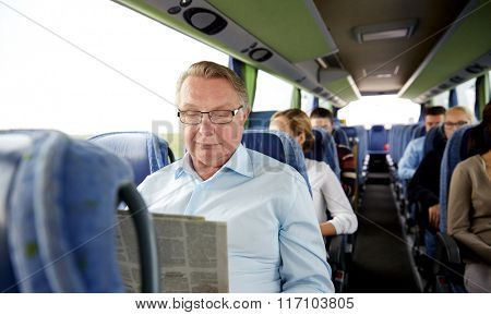 happy senior man reading newspaper in travel bus