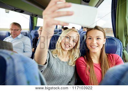 women taking selfie by smartphone in travel bus