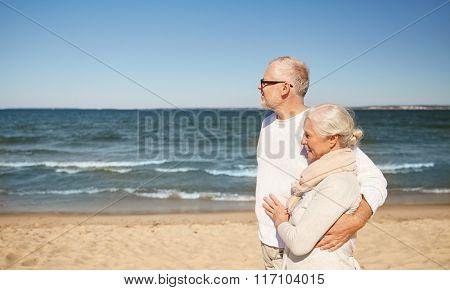 happy senior couple walking along summer beach