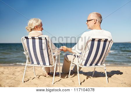 happy senior couple in chairs on summer beach