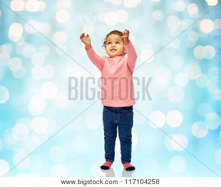 little baby girl playing with soap bubble