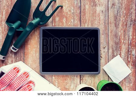 close up of tablet pc and garden tools on table