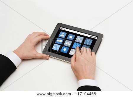 close up of man hands with app icons on tablet pc