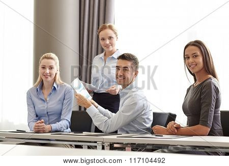 smiling business people with papers in office