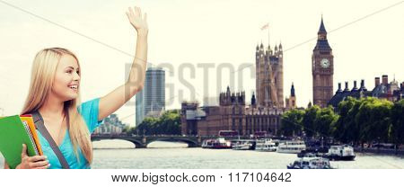 student with folders waving hand over london city