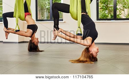Antigravity yoga exercise. twwo girls