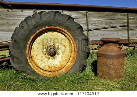 A milk can tire, and weathered old manure spreader