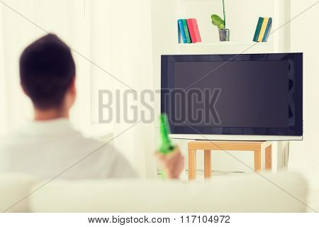 man watching tv and drinking beer at home