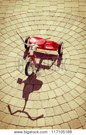 Red Tricycle With Shadow On Sunny Stone Patio