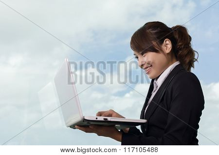 Asian business woman work with laptop near the window in hotel room.