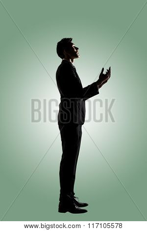 Silhouette of Asian businessman praying, full length portrait isolated