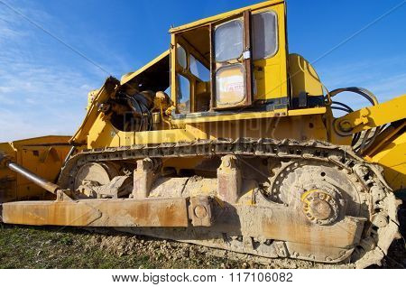 Yellow bulldozer in a field with blue sky.