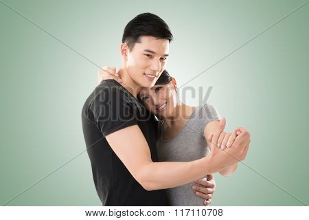 young Asian couple dancing with smiling face.