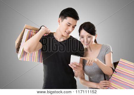 young Asian couple shopping and looking at cellphone