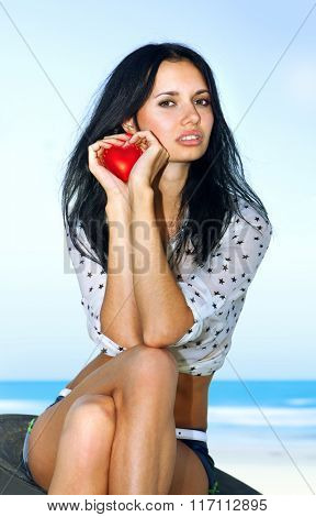 beautiful woman shows red heart in hands