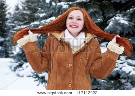Winter woman outdoor portrait show long red hair, snowy fir trees background