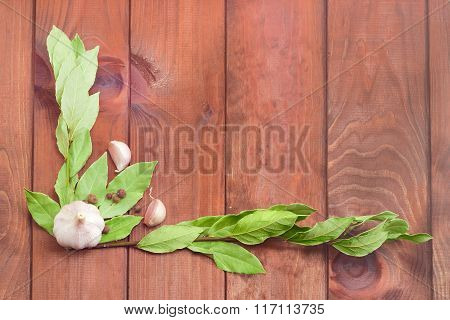 Branches Of A Bay Laurel, Garlic, Allspice On Wooden Surface