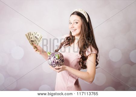 Beautiful young lady holding US banknotes and piggy bank