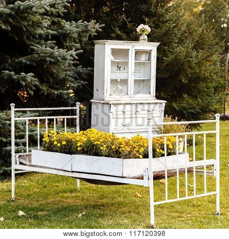 Bed With Yellow Flowers And Old White Cupboard On Background Of Firs Outdoors