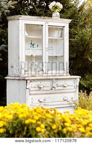 Yellow Flowers And Old White Cupboard On Background Of Firs Outdoors