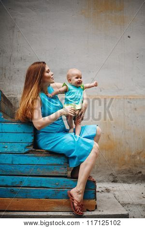 Cute Happy Toddler Sitting On Loving Mother`s Knees