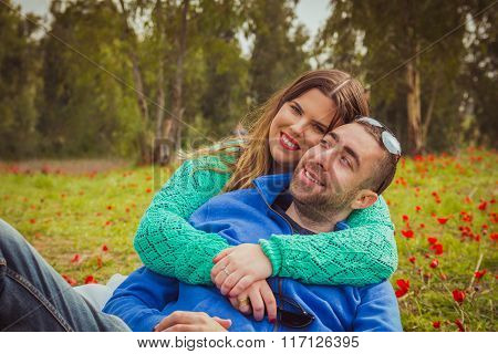 Young couple sitting on the grass in a field of red poppies and smiling at the camera.