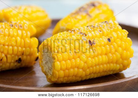 Grilled corn on the cob with salt and butter on a wooden plate