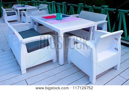 White Rattan Wicker Armchairs And Tables On Summer Terrace In Twilight