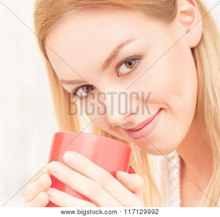 Lady with a cup of tea indoors