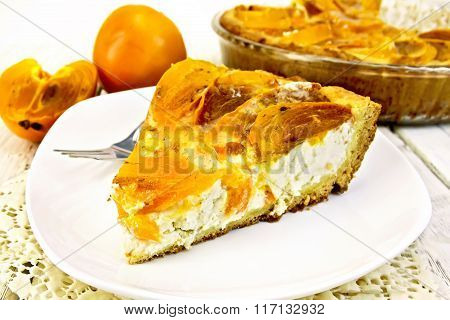 Pie with curd and persimmons in white plate on napkin silicone
