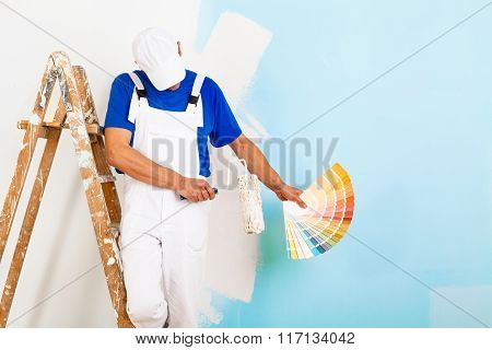 Painter With Paintroller Showing A Color Palette