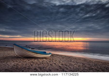 Boat And Sunrise With Dramatic Cloudscape