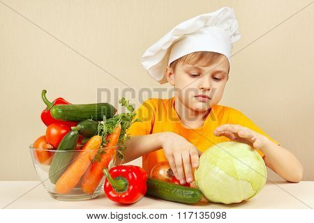 Little funny boy chooses vegetables for salad at table
