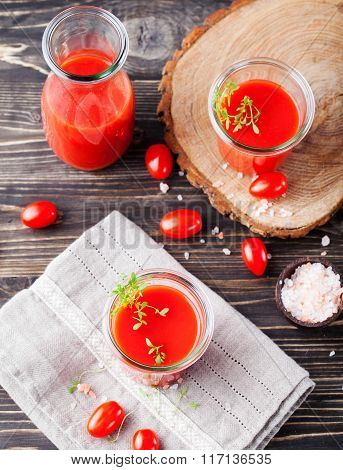 Tomato juice in glass with cress salad, fresh tomatoes on vintage wooden cutting board and grey towe