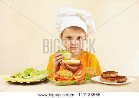Little boy in chefs hat puts salad on sandwich