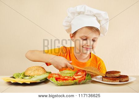 Little boy in chef hat puts meat on hamburger