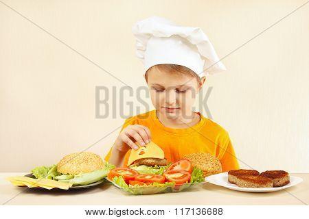 Young chef puts cheese on hamburger