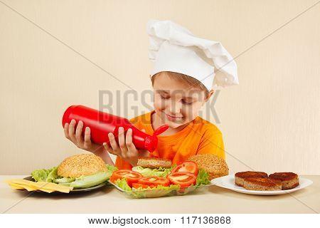 Little smiling boy in chefs hat puts sauce on hamburger