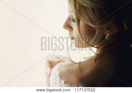 Beautiful Blonde Wedding Bride In Make-up And Veil In A White Dress Close-up