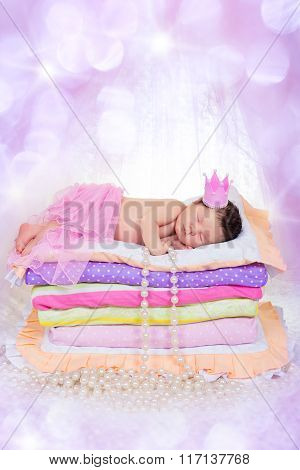 Newborn Baby Girl In A Crown Sleeping On The Bed Of Mattresses. Fairy Princess And The Pea