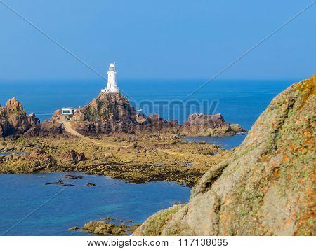 La Corbiere Lighthouse On The Rocky Coast Of Jersey Island