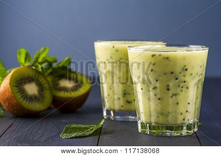 Glass of homemade smoothie with kiwi banana and mint leaves