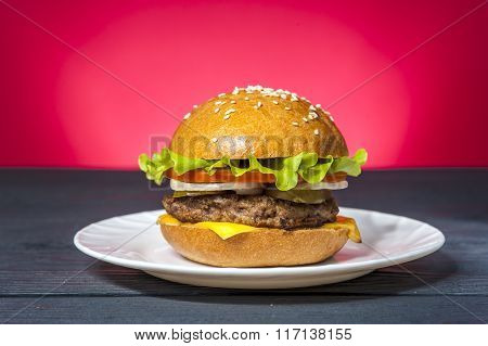 Appetizing hamburger with vegetables on white plate on wooden table. Fast food junk food. Unhealthy food concept.